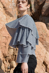 Architectural top from black gingham stripes. Asymmetric neckline with self tie detail at side neck. Exaggerated ruffle panel at one shoulder sleeve.