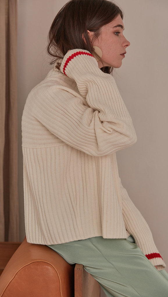 Jupe Sweater in Ivory. Cowl neck ribbed sweater with pointed dropped shoulder seams and extra long sleeves. Designed to be loose fit.