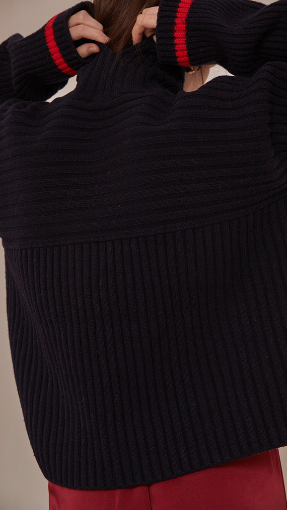Jupe Sweater in Navy. Cowl neck ribbed sweater with pointed dropped shoulder seams and extra long sleeves. Designed to be loose fit.
