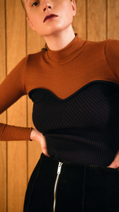 The Kaare Top in Black/Brown. With a seamless mock neckline, heart shape bustier layered in lightweight knit top. Designed to be slim fitting. Pulls on.
