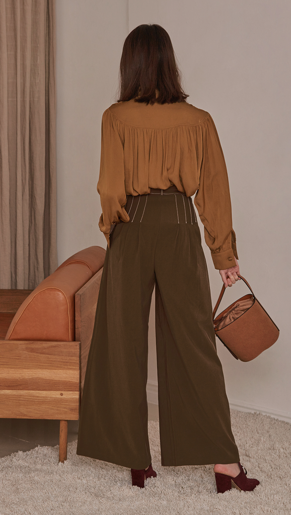 Kahn Pant, a stride wide in the darkest khaki shade. High waisted raglan pleated, deep waistband, zipper fly and tab closure. Fitted at the waist with leaving the fluidity of the trousers to flow.