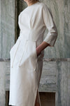 The Kaveh Dress in White, featuring three-quarter sleeves with stitching details, ruched at waist, two slant pockets. Concealed zip fastening at the back. Fitted at waist. Side slits.