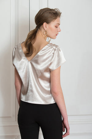 The Keena Top in Champagne featuring deep V-neckline, ruched short cap sleeves, button down closure.