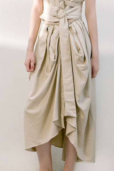 The Keria skirt in draped front skirt with detachable sash belt. Concealed back zip closure. Mid length.