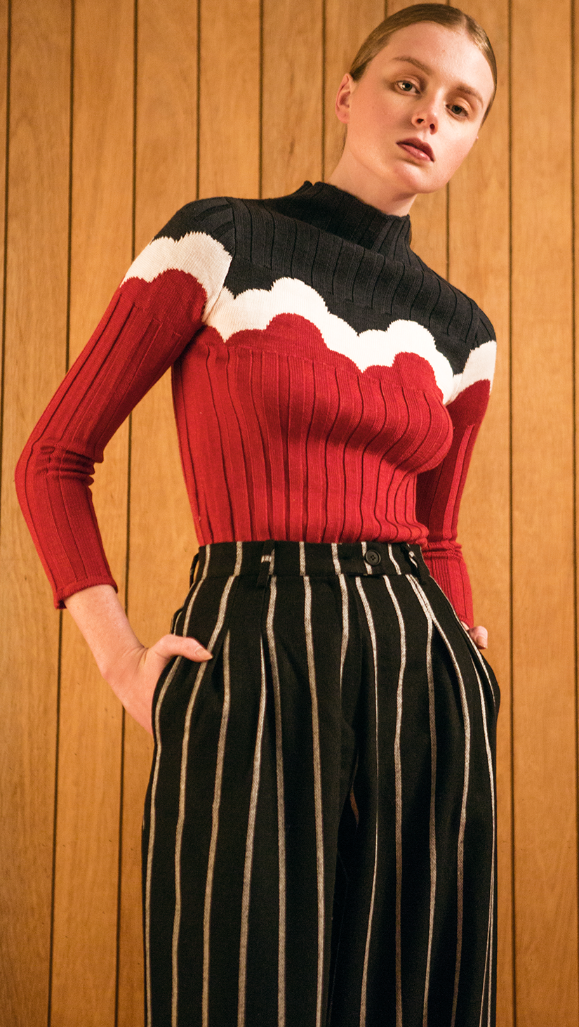 The Kismet Knit in red/black, a lightweight ribbed sweater. With a seamless mock neckline, raw edges. Pull on. Starchy fabric.