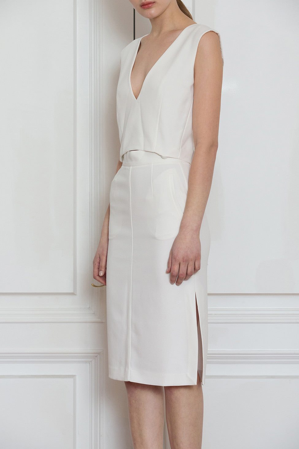 The Kole Dress in White, featuring deep V-neckline, sleeveless, open back in eyelet detailing with self-tie. Detachable snap button closure that can be worn separately as top and skirt. Skirt has a concealed zip fastening at the back.