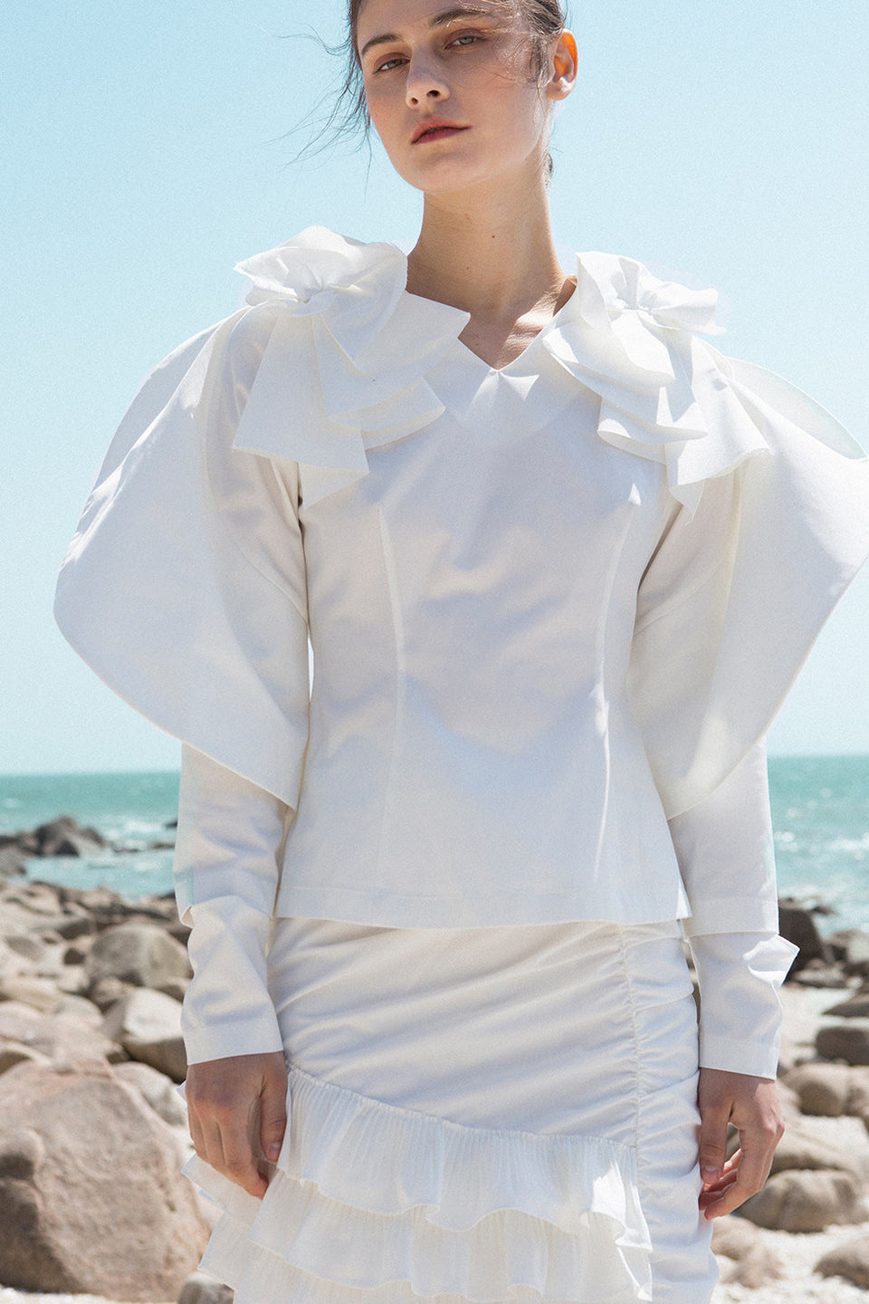 The Krikoi Top in White featuring v-neckline, swirling petal sleeves, slit at cuffs with zipper. Center back zip closure. Slim fit at bodice.
