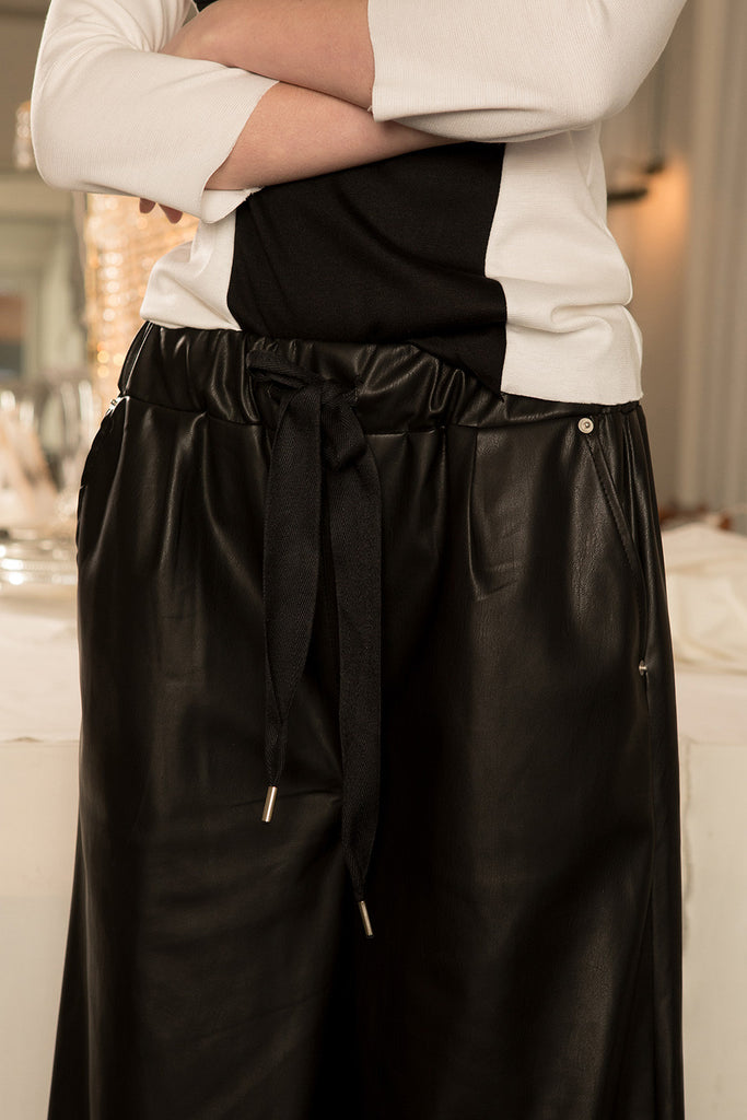The Kuri Pant in Black featuring elasticated waistband with drawstring, slanted two pockets. Wide-leg silhouette.