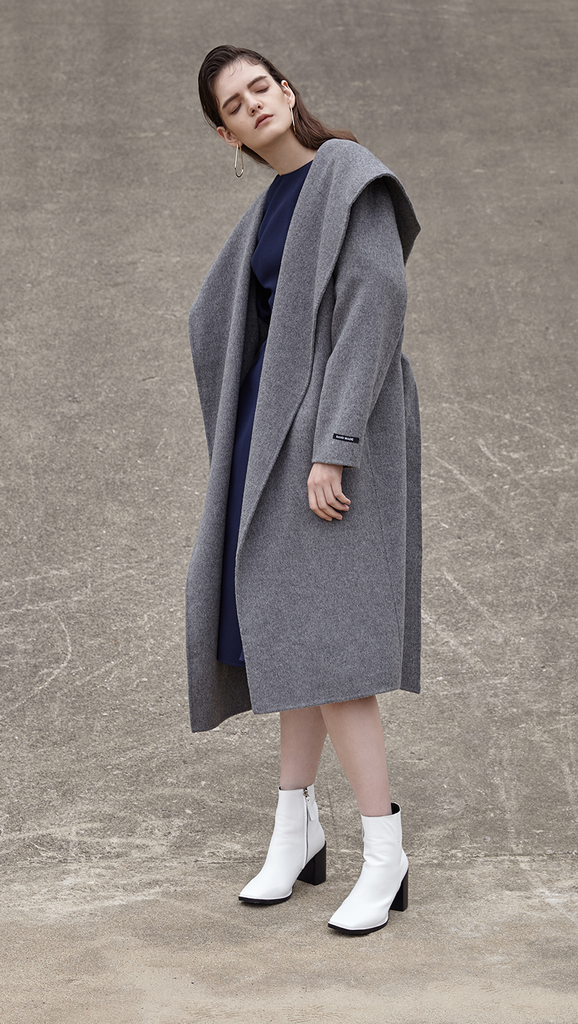 The Handmade Leevia Coat in grey. With a funnel collar, long sleeves, self-tie belt at natural waist. Side seam pockets, wide hoodie, belt loops. Oversized cut. Can be worn open or cinched.