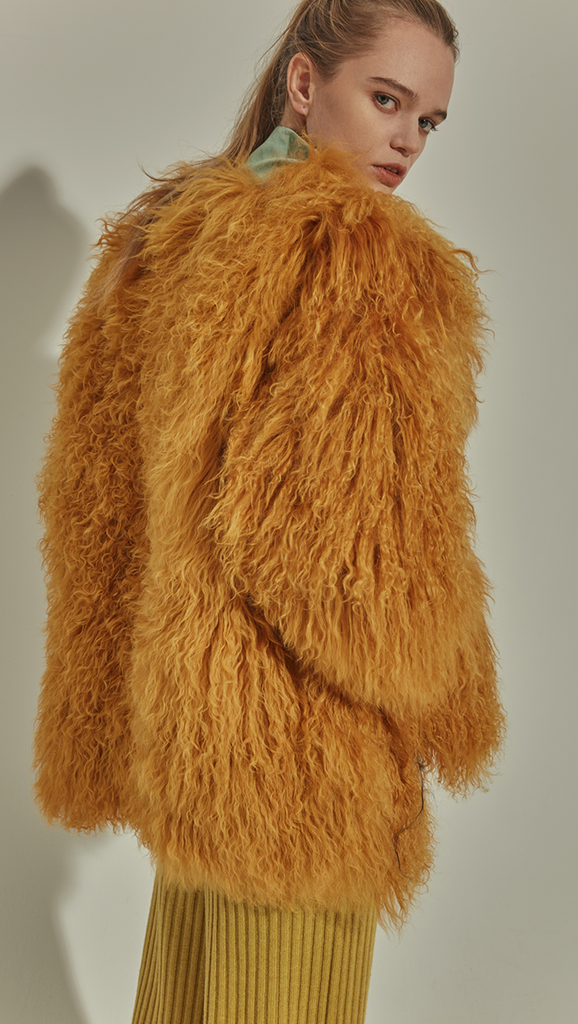 The Lellyn Fur Coat in Mustard. Exaggerated furry long sleeves, hook and eye closure. Oversized fit. Fully lined.