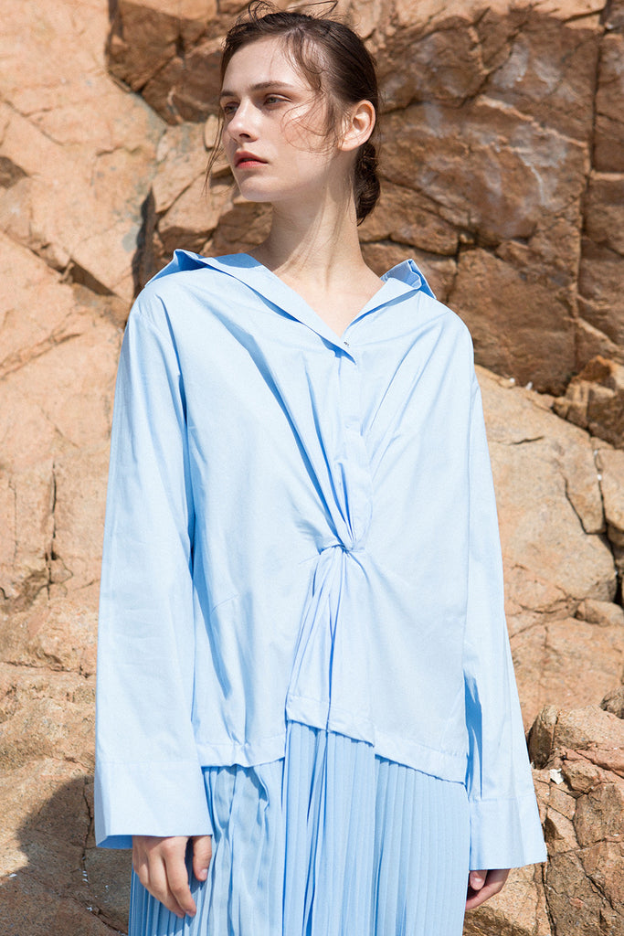 The Leslie Dress in Blue featuring stylized snap button-down shirt dress. Wide v-neckline, spread collar, full-button placket with twisted detailing. Detachable A-line shaped wide belt with concealed zip closure at waist. Dropped shoulder. Long bell sleeves with wide button cuff. Long silhouette. Oversized fit.