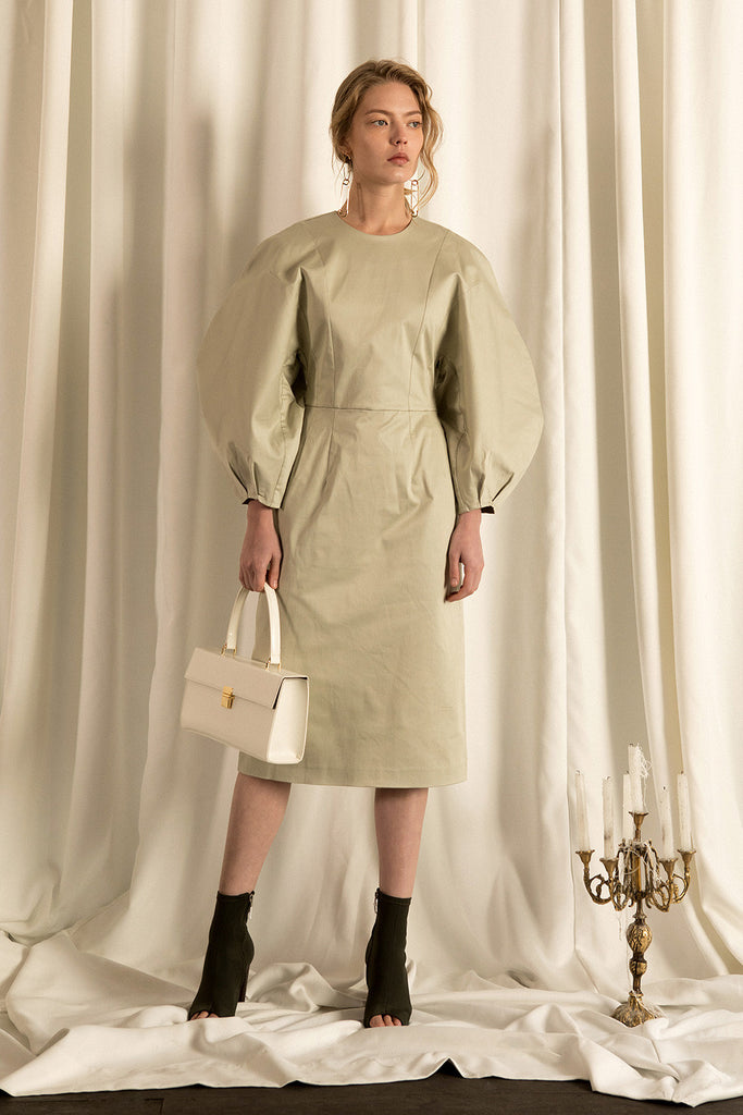 The Leyla dress in Olive, featuring round neckline, long puff sleeves with raglan detail at cuff, concealed zip fastening at the back. Fitted bodice.