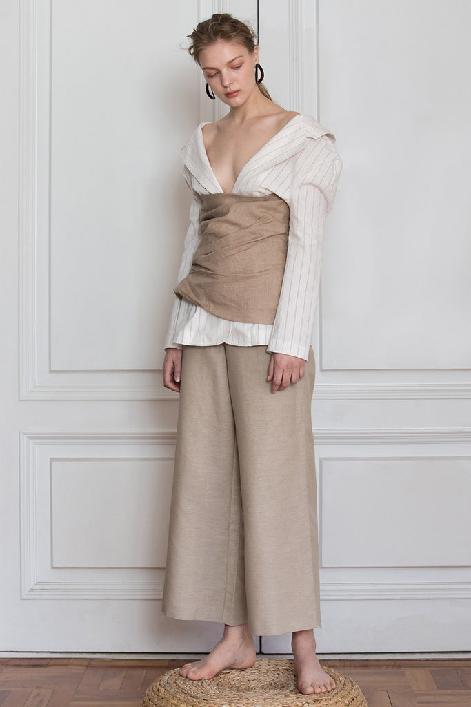 The Souris Jacket in Ivory with brown striped, featuring a-line jacket with fitted waist with one button closure, vertical pleating, open collar with back tie. Fitted at waist.