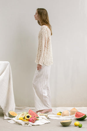 The Loe fishnet knit in Ivory featuring deep V-neckline, long sleeves. Pull on. Comfortable silhouette.
