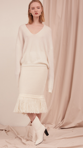 The Lilia Knit in off white. Features long sleeve, deep V-neckline, dropped shoulder. Pull on. Slightly loose fit.