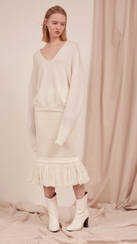 The Losara Skirt in ribbed knit off-white. With gathered elastic waistband, tassels hem, deep v back slits.