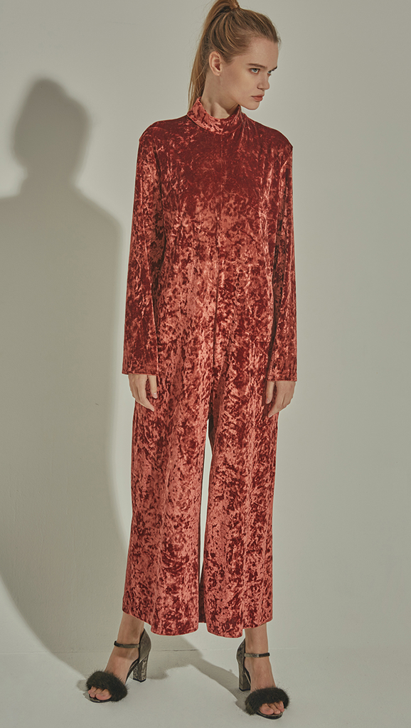 The Lynn is a loose fit jumpsuit in lustrous velvet. With a turtleneck collar, long sleeves and concealed zip closure at back. Russet Brown. Relaxed fit.