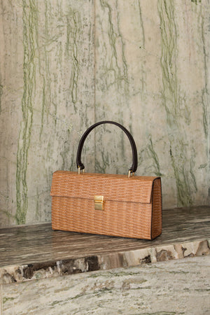 Malmo rattan bag in Brown. Top carry handle. Main compartment with front flap magnetic snap tab closure. Detachable shoulder straps.