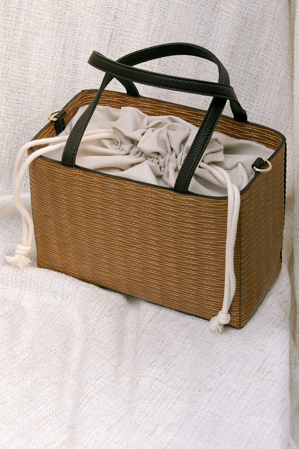 Mamba bag in Brown. Woven straw basket bag with fabric insert. Top handles. Detachable shoulder straps.
