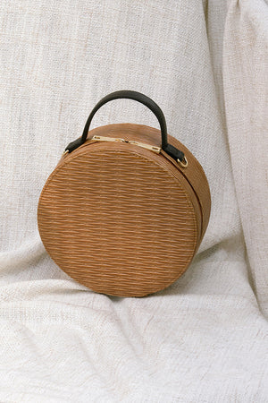 Marais bag in Brown. Woven round straw basket bag with fabric insert. Top handles. Detachable shoulder straps.