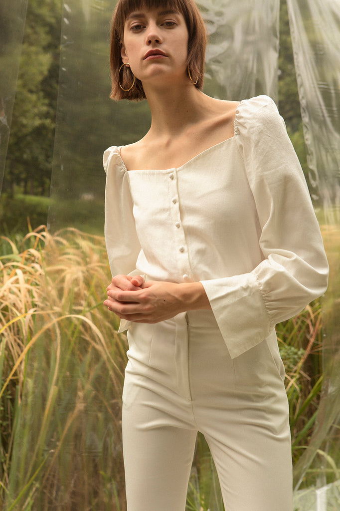 Sculptural blouse in bateau neckline. Ruched details at shoulders. Voluminous sleeves with flounce cuffs and single button closure. Button down closure. Can be styled in off-the-shoulder silhouette.