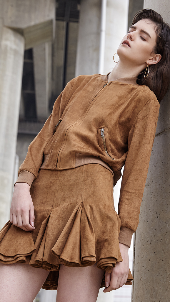 The Meera Suede Set in camel jacket and skirt. Jacket has a single zip closure at front, side pockets with zipped opening, no collars. Skirt has a flared hem with back zip closure. Lightweight. Slim fit.
