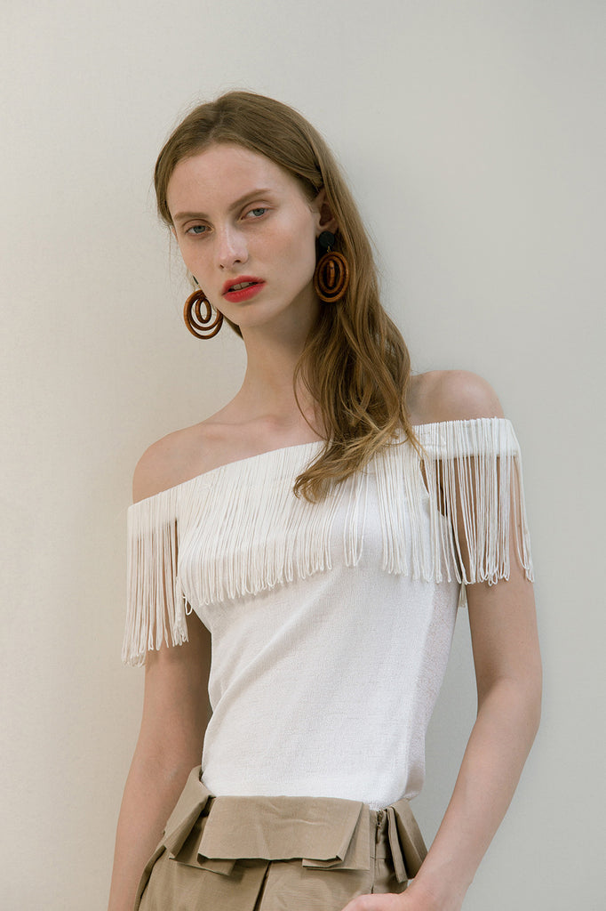 The Miquela Top in White featuring off-the-shoulder silhouette with tassel. Pull on. Slim fit.