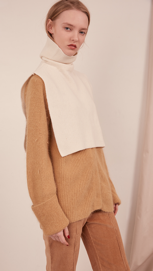 The Muir Turtleneck Knit in ivory with no sleeves. Pull on
