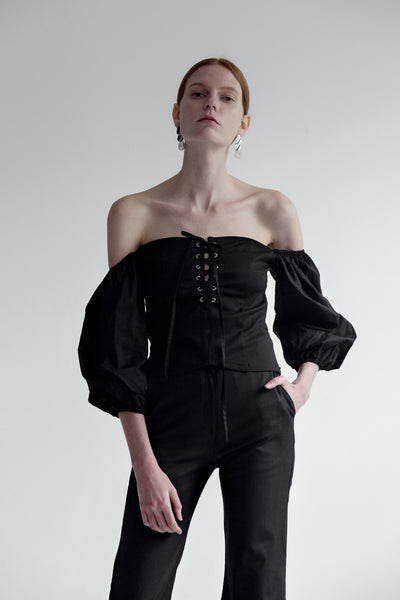 The Nahera Top in black featuring off-the-shoulder with long sleeves, self-tied closure and concealed zip opening along side. Cropped length.