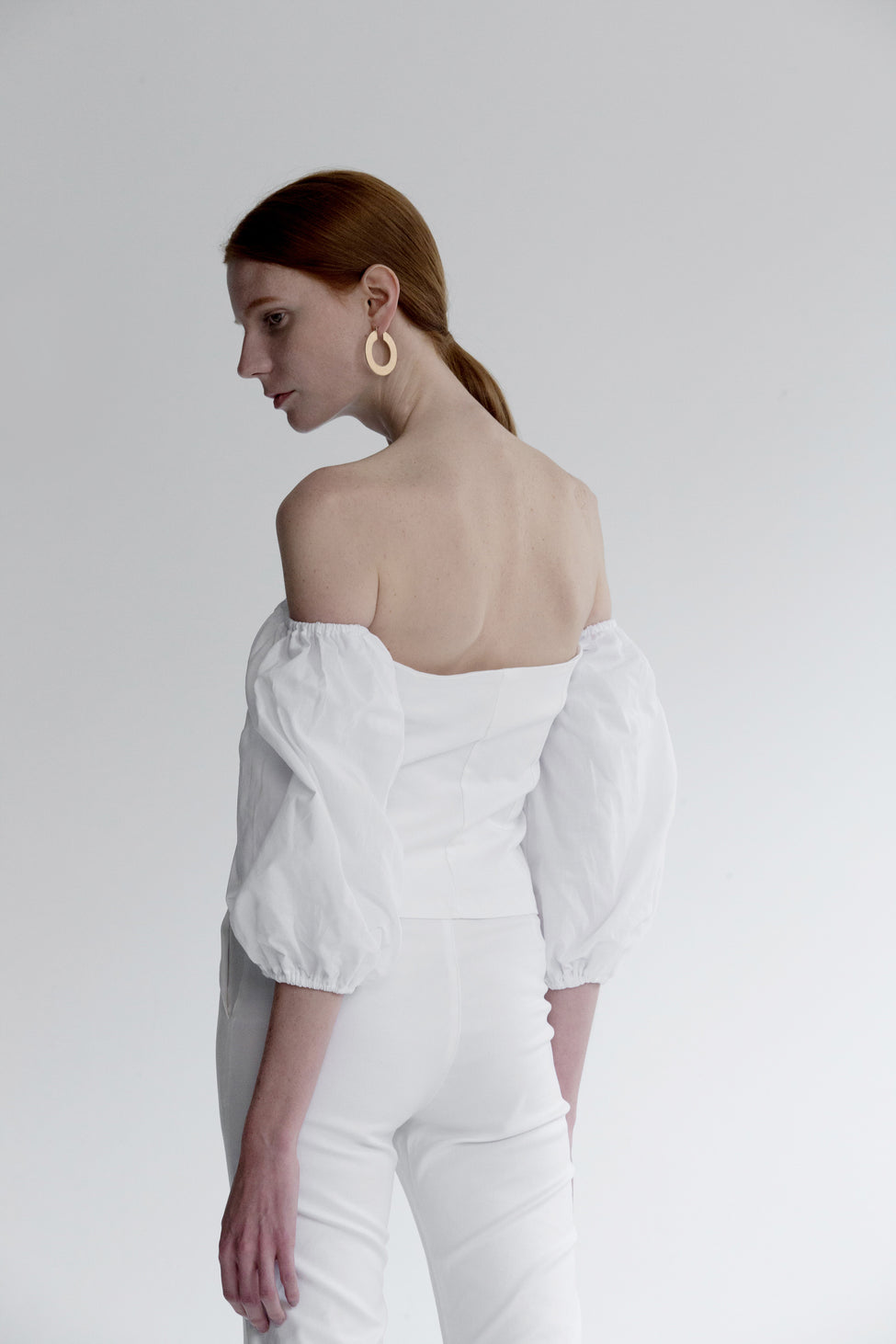 The Nahera Top in white featuring off-the-shoulder with long sleeves, self-tied closure and concealed zip opening along side. Cropped length.