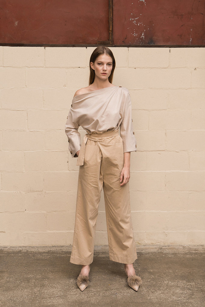 Draped trousers featuring high rise, concealed side zip closure with wrap-look tie adjustment. Darts from back waist. Relaxed straight leg. Full-length. Unlined.