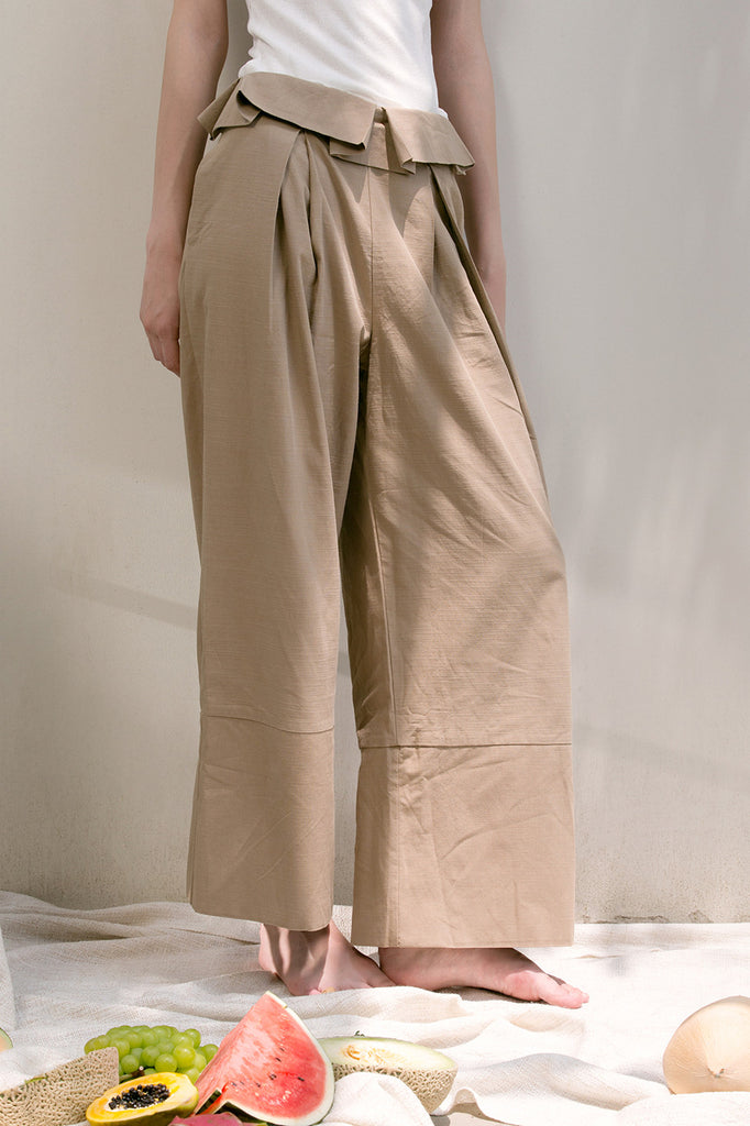 The Noelle Pant in brown featuring pleated front with origami design, two slant pockets. Lightweight.