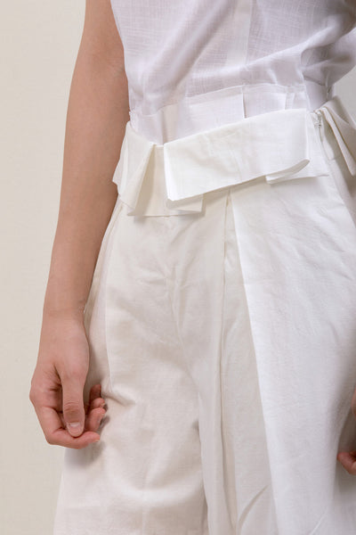 The Noelle Pant in white featuring pleated front with origami design, two slant pockets. Lightweight.