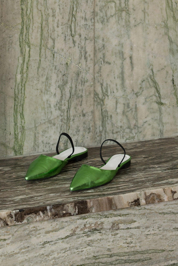 The Pajama sandal in neon metallic green. Almond toe. Thin strap across upper. Slip-on design.