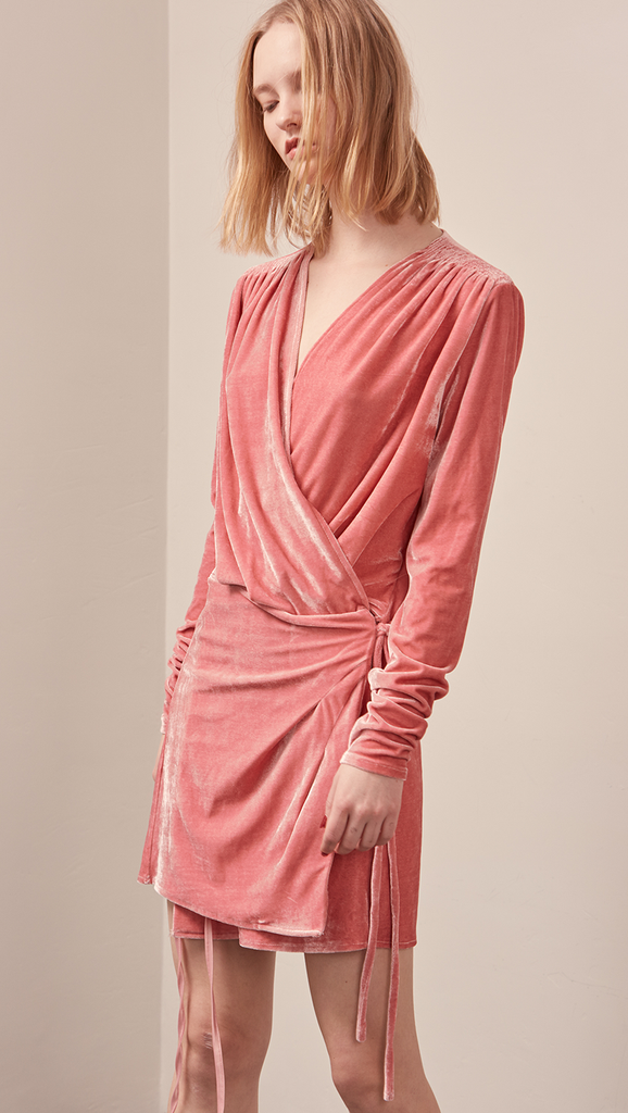 The Reve Velvet Dress in Pink. Featuring dee[ V-neckline, ruched shoulder sleeves, wrap front with self-tie at waist. Stretchy fabric.