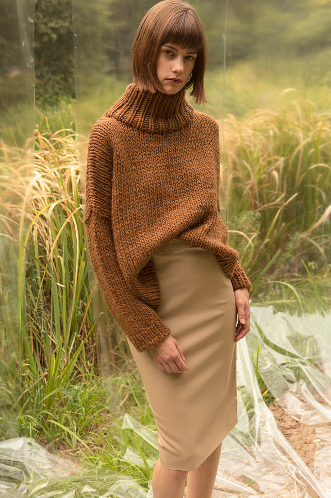 Pullover sweater with chimney collar with dropped shoulders. Gently tapered long sleeves. Slightly cropped. Boxy silhouette. Softy, bulky garter stitch knit. Relaxed fit.