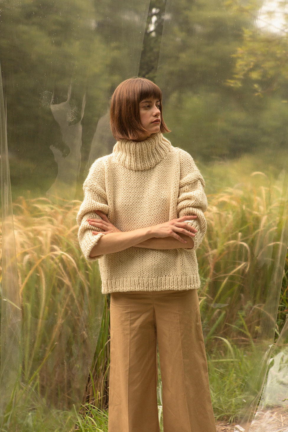 Open knit with turtleneck collar with dropped shoulders. Gently tapered long sleeves. Slightly cropped. Boxy silhouette. Relaxed fit.