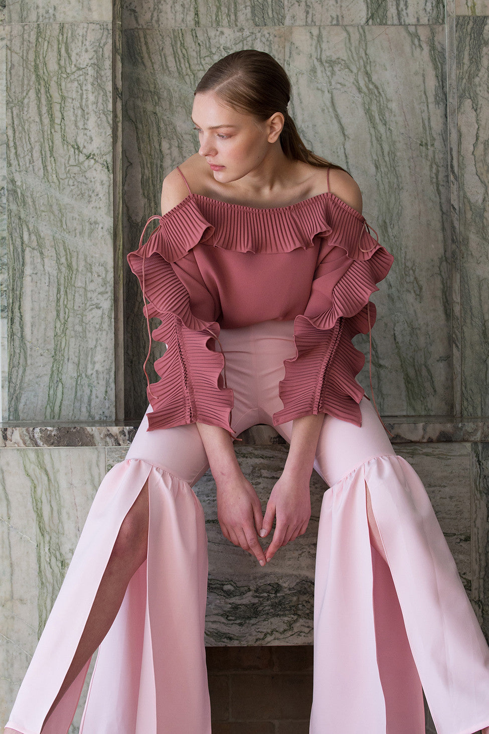 The Cheysa Pant in Pink featuring peplum leg trouser, gently flare out hem with side slits. Slim-fitting at thigh. High rise. Centre-front concealed zip fly and hook closure.