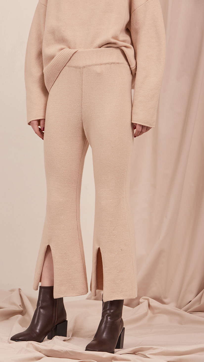 The Roscoe Pant in cream beige. Cropped length with deep V slit, gathered elastic waistband. Slightly dropped crotch. High rise.