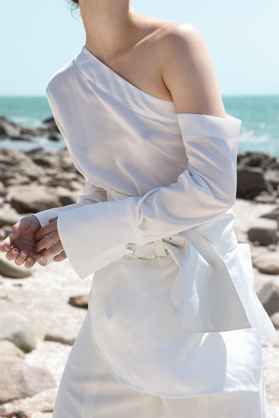 The Roslyn Top in white featuring one shoulder with long sleeves, pearl hardware button at cuffs, elastic band at back. Pull on.