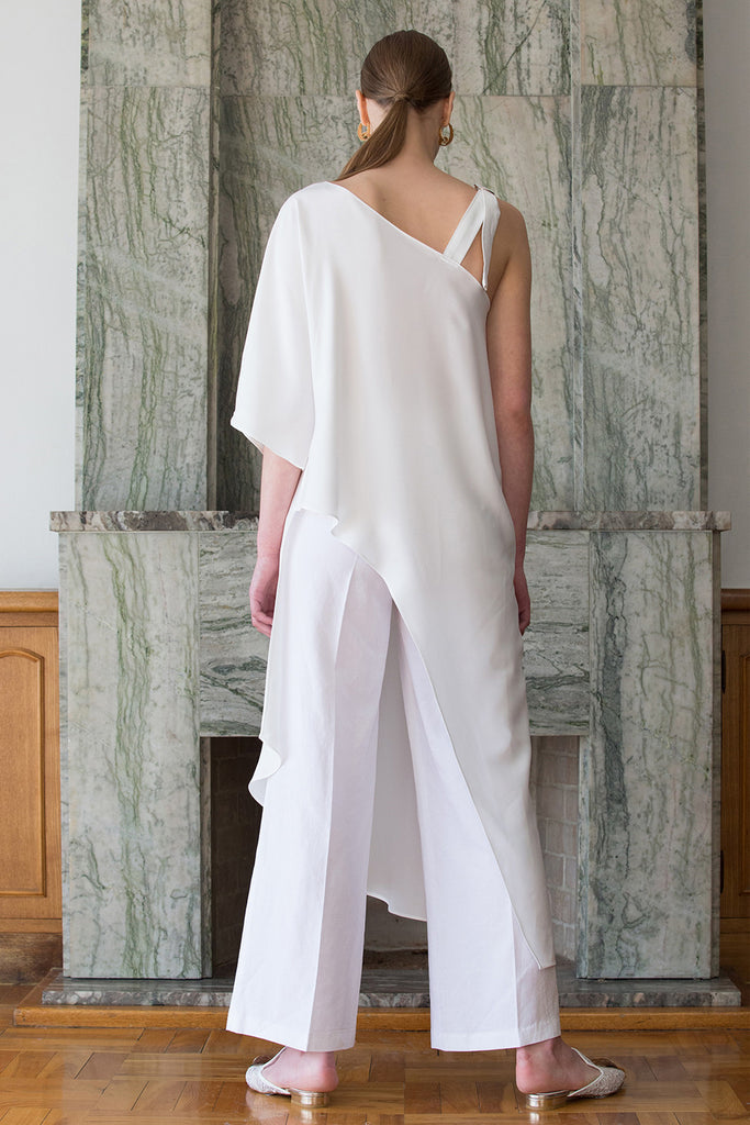 The Rowe Tunic in White. Cut out at one shoulder with D-ring adjustment. Asymmetric hem. Semi sheer. Pull on.