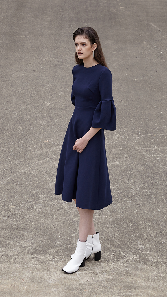 Roxette Dress in navy. With a voluminous flounce sleeves in 3/4 length, round neckline, silk blend insert in contacting collar - bold orange. Below-the-knee length. Hidden zip closure along back. A-line silhouette.