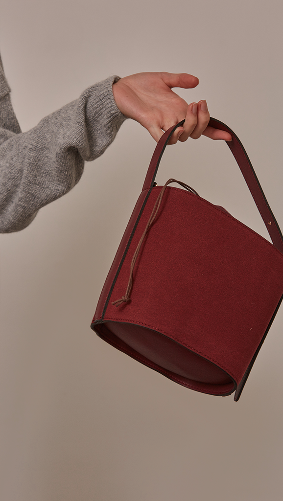 Seed Bucket bag in Burgundy. Main compartment with adjustable strap, detachable shoulder strap, interior pocket with zipper compartment. Structured bottom.