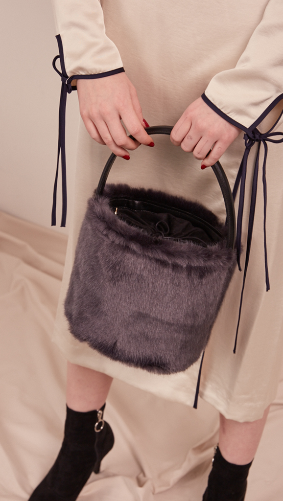 Seed Furry Bucket bag in Lava Grey. Main compartment with adjustable strap, detachable shoulder strap, interior pocket with zipper compartment. Structured bottom.