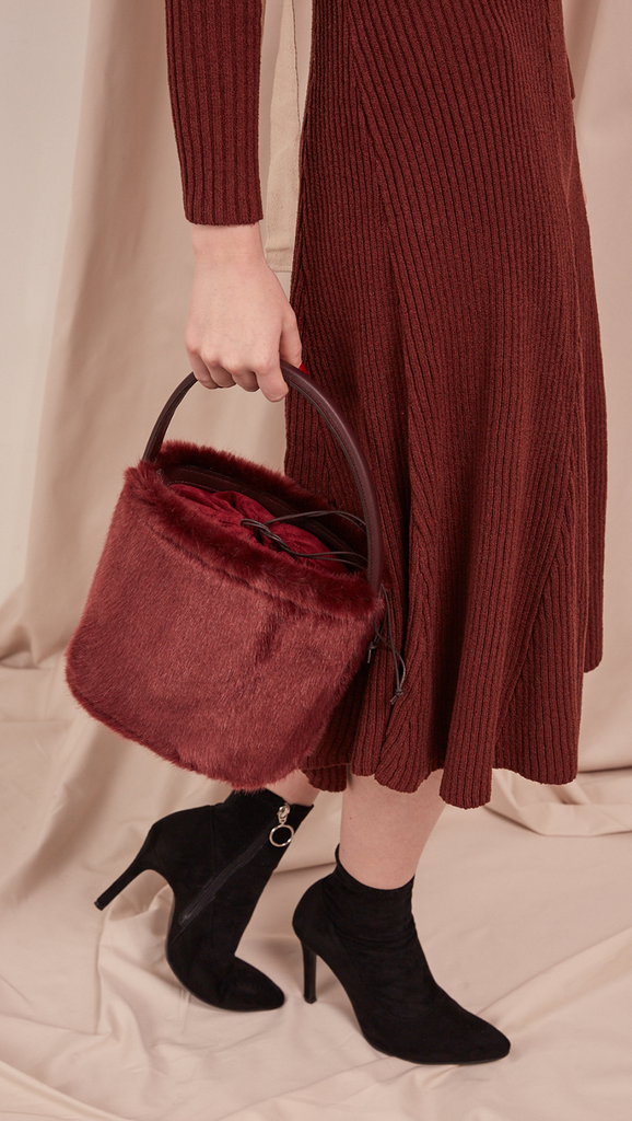 Seed Furry Bucket bag in Wine. Main compartment with adjustable strap, detachable shoulder strap, interior pocket with zipper compartment. Structured bottom.