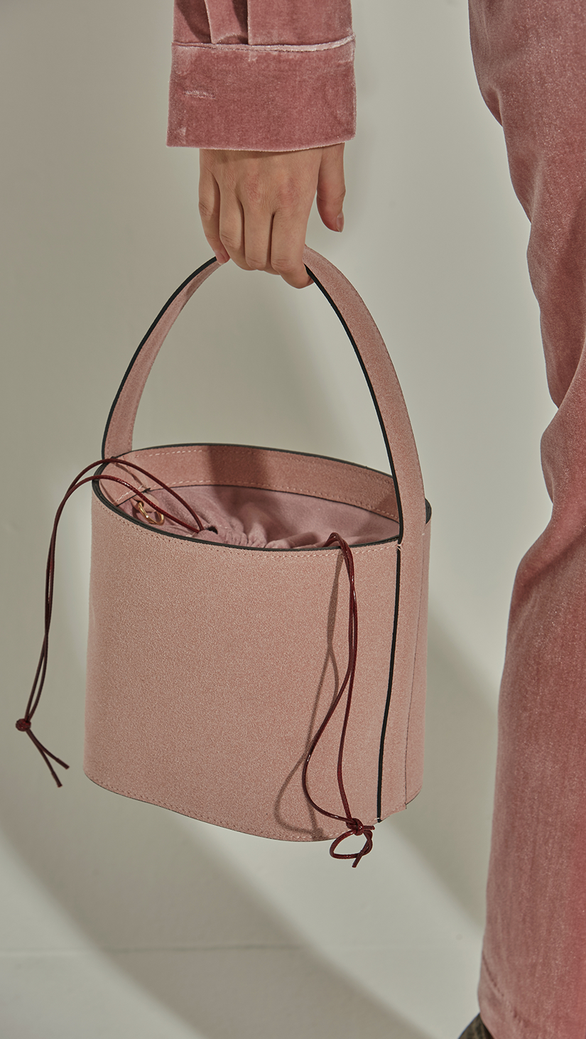 Seed Bucket bag in Pale Pink. Main compartment with adjustable strap, detachable shoulder strap, interior pocket with zipper compartment. Structured bottom.