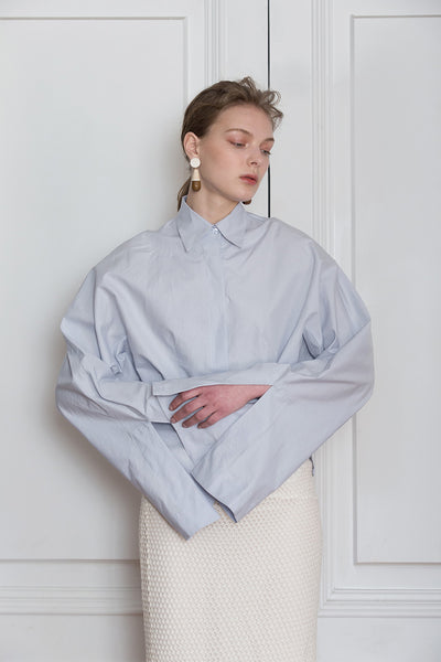 The Selina Shirt in Blue featuring classic button down with full length wide sleeves. Button closure at cuffs. Dropped Shoulder.