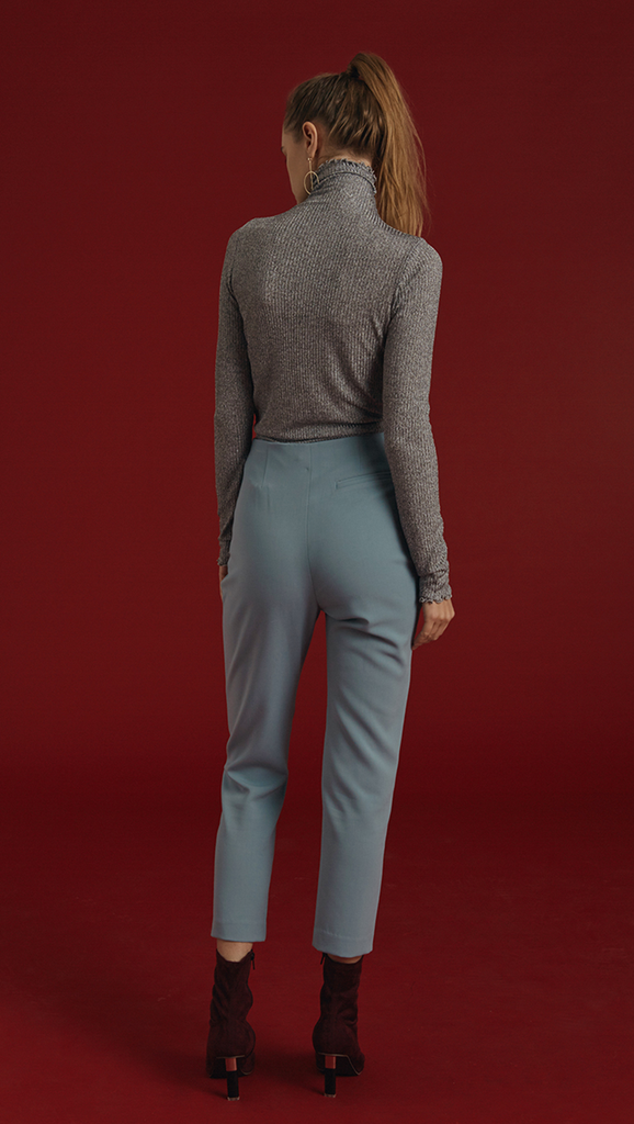 The Siena Pant is high waisted, cropped carrot trousers with gold hardware detailing in Airy Blue. Concealed zip closure along side. No pockets.