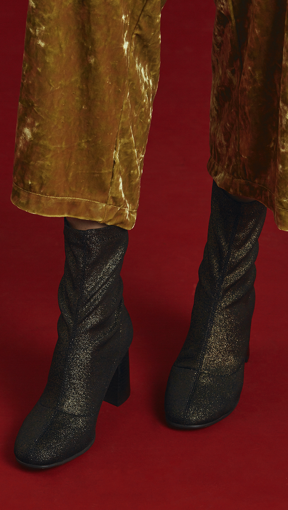 Stretch shiny fabric ankle boots in gold metallic. Matching topstitching detail in the centre. Pull-tab at the back. Rounded toe. Rounded heel. Ankle length.