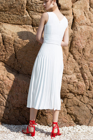 The Simma Dress in White, featuring v-neckline, sleeveless, removable wide belt, pleated skirt. Concealed zip fastening at the back. Fully lined.